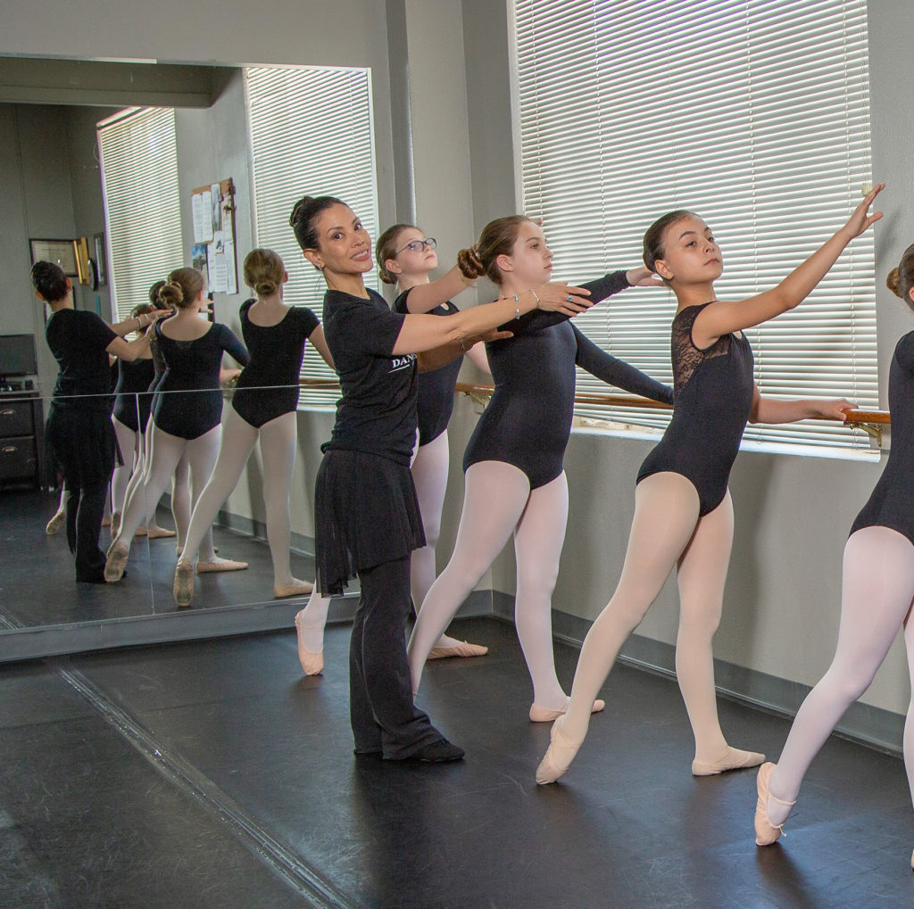 Ballet teacher and students lined up at the barre